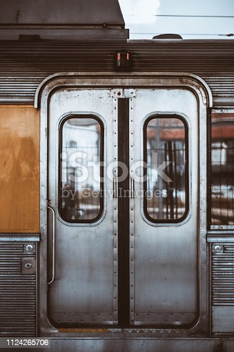 Vertical shot of the metal grungy closed automatic doors of a chrome carriage trim of a European suburban train with windows, two buttons for opening, handhold, and a round lock below