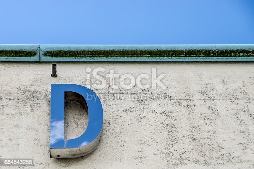 Metallic letter 'D' on the wall of a building, reflecting the cloudscape above.  Belfast, Northern Ireland.