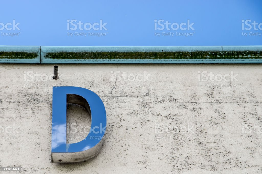 Metallic letter 'D' reflecting cloudscape above stock photo