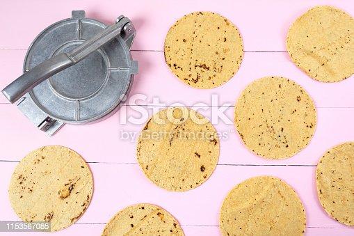 Metallic manual machine tortilla press on wooden pink background