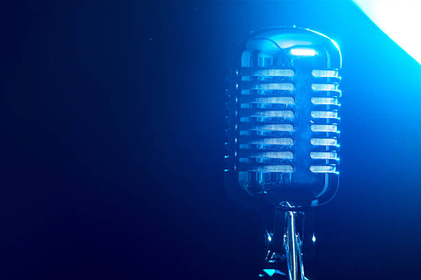 Metallic microphone isolated on a blue background stock photo