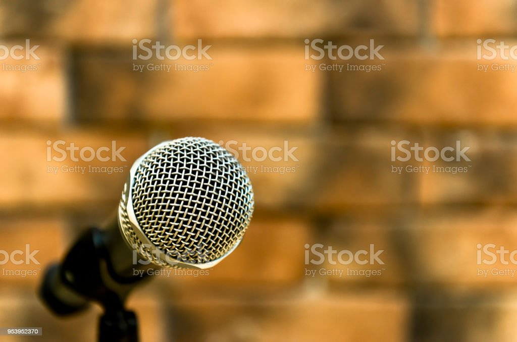 Metallic microphone on the stand beside brick walls stock photo