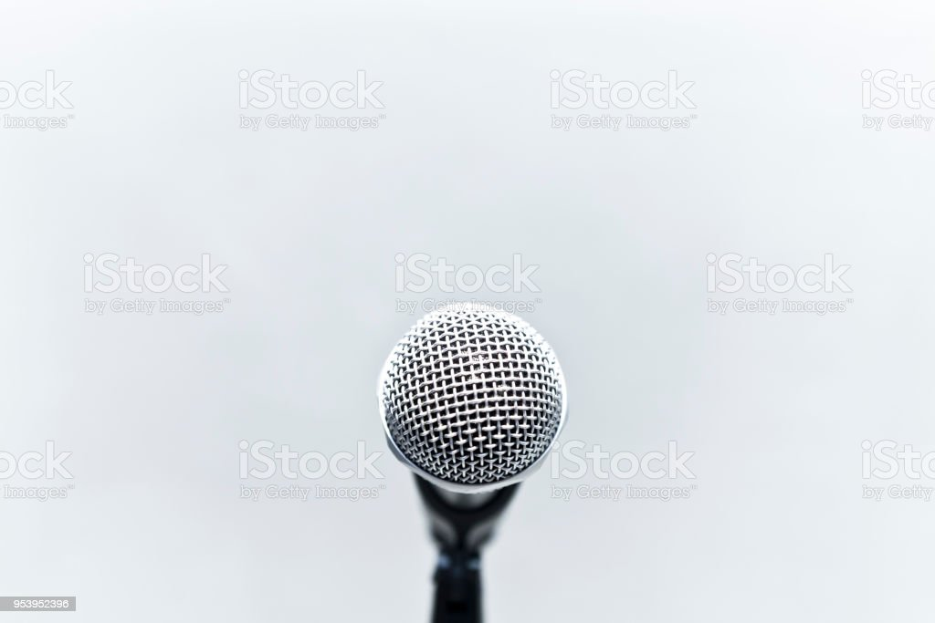Metallic microphone on the stand with grey cement wall stock photo