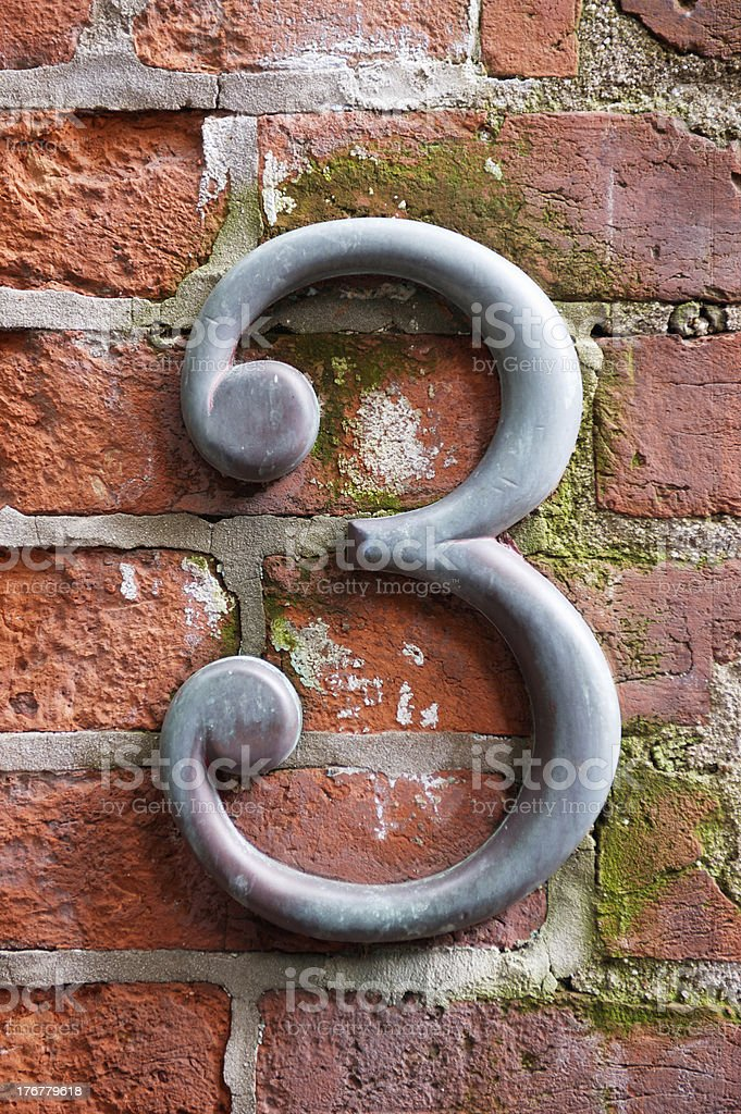 Metallic No. 3 contrasts with brick texture. royalty-free stock photo