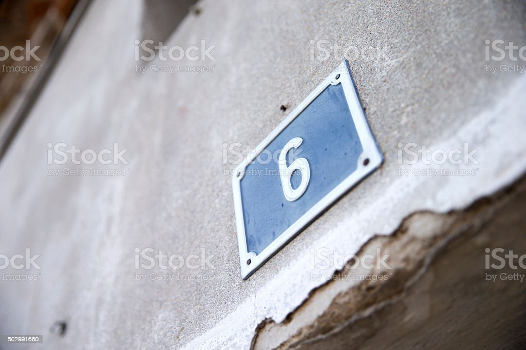 Metallic number of house on wall stock photo