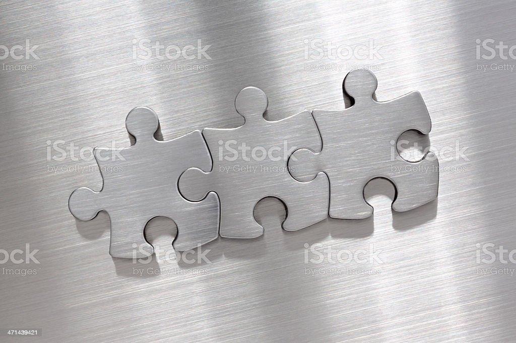 Metallic puzzle pieces stock photo