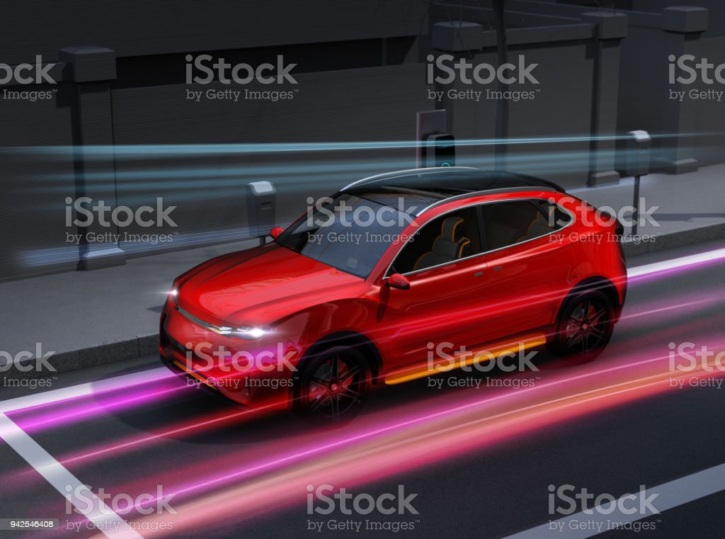 Metallic red electric SUV charging at parking lot with charging station in the street stock photo