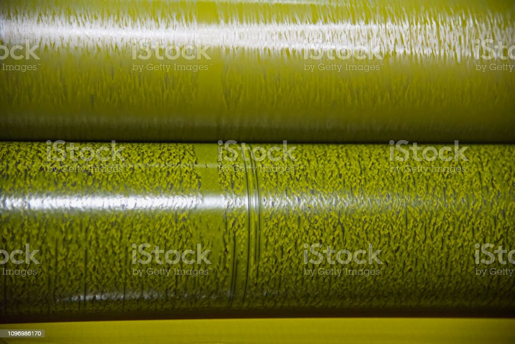 Metallic roll of yellow colours of a printing machine stock photo