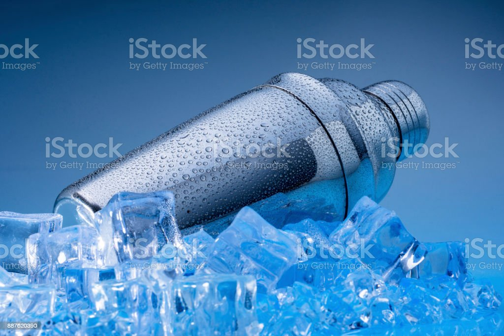 metallic shaker with drops of water on ice with blue background stock photo