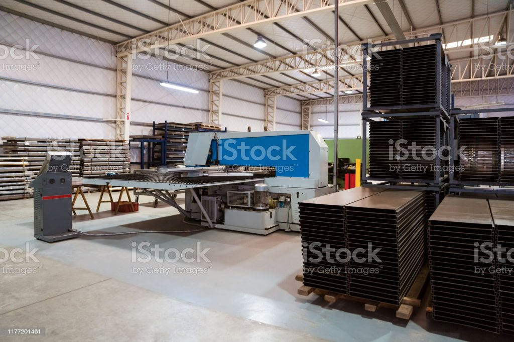 Metallic sheets stacked on rack by puller machine Puller machine by stacked metallic sheets. Equipment are arranged by machinery in manufacturing factory. Absence Stock Photo