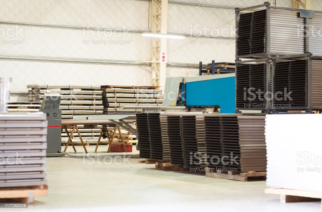 Metallic sheets stacked on rack in industry Metallic sheets stacked on rack. Equipment are arranged in factory. Absence Stock Photo