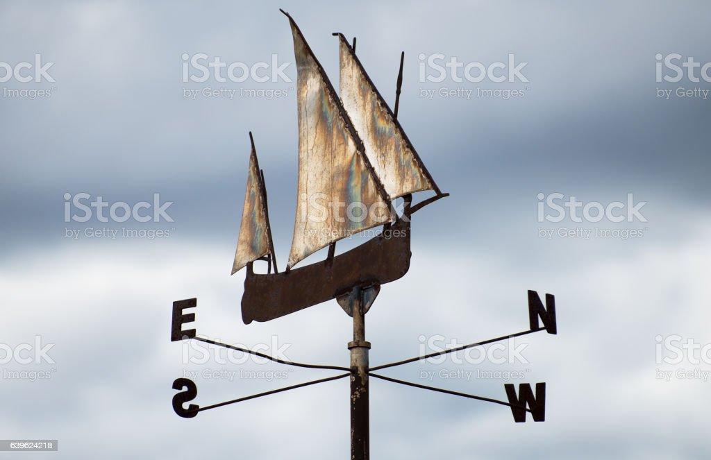 Metallic ship weather vane on sky background. stock photo