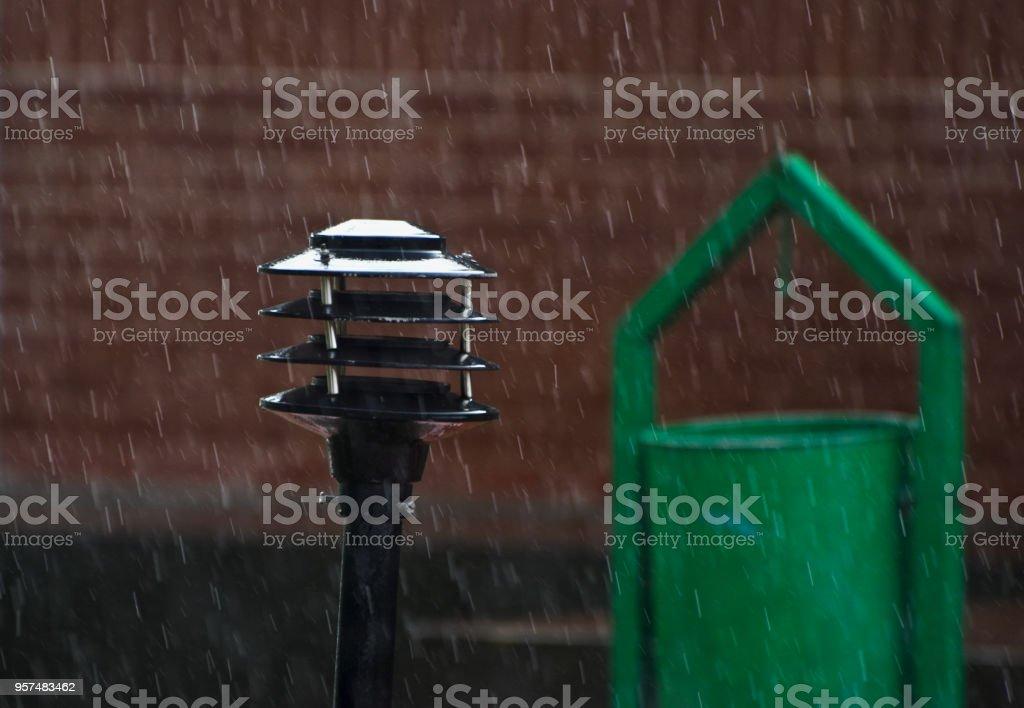 A metallic street lamp shade in the rain unique photo stock photo
