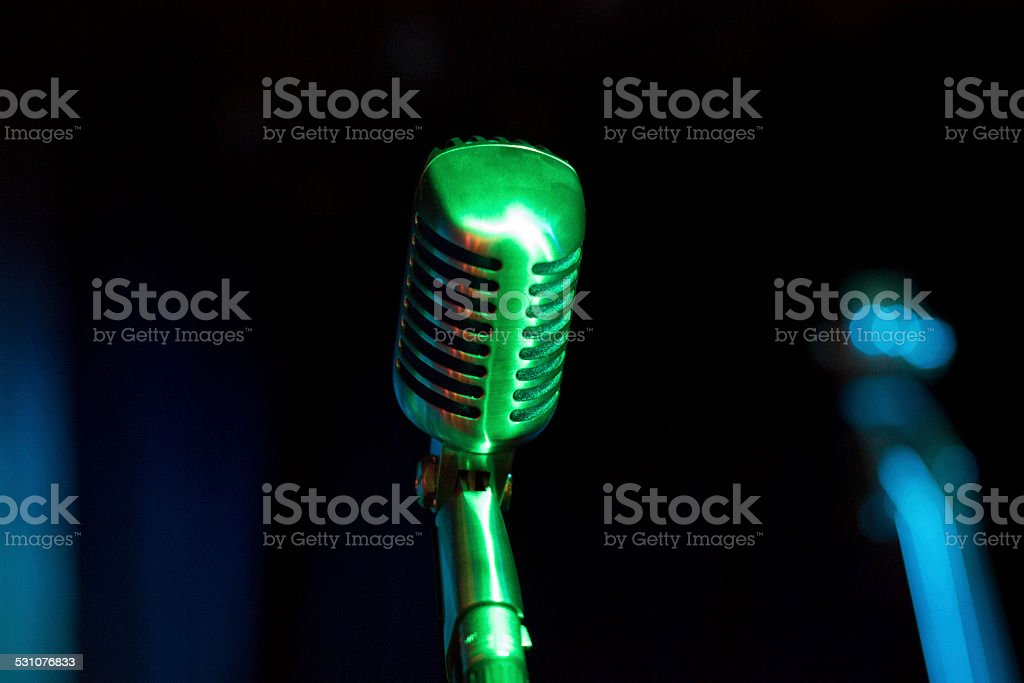 Metallic Vintage Microphone on stage in green light stock photo