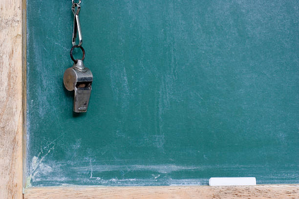 A metallic whistle hanging by the chalkboard stock photo