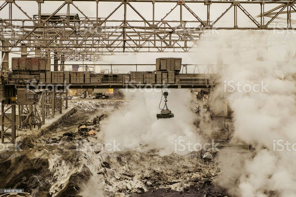 Metallurgical hot slag dump with magnetic overhead crane. Mining heavy industrial background. stock photo