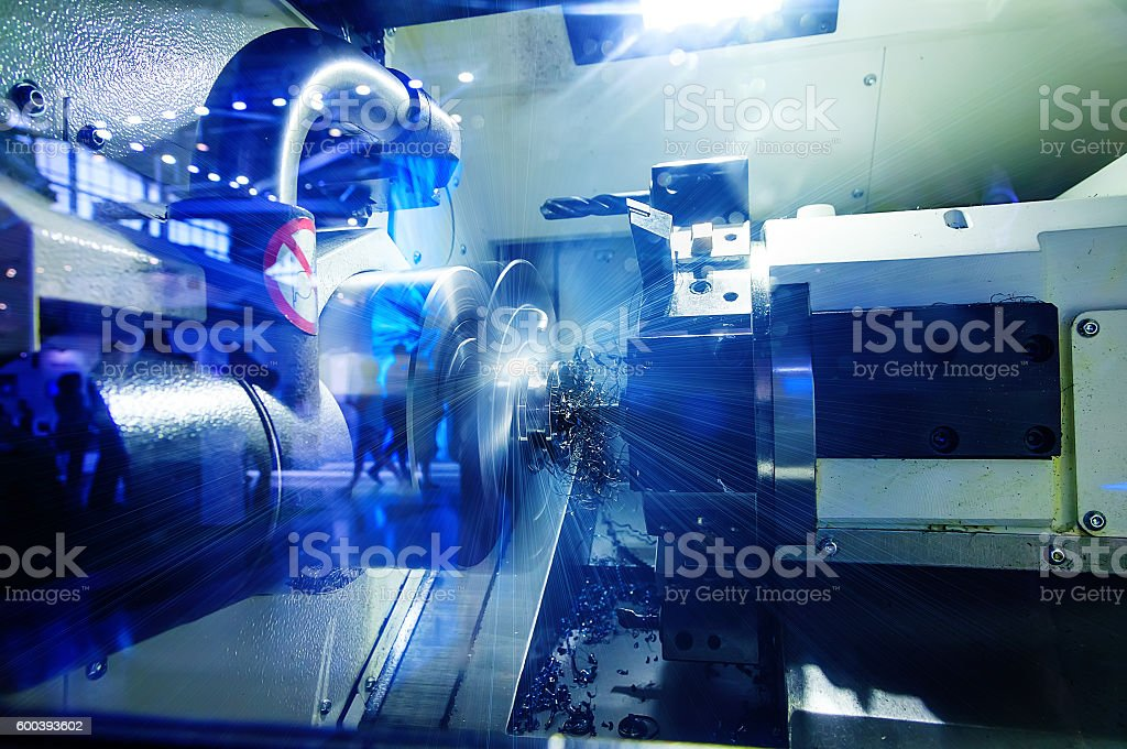 metalworking industry: finishing metal working on lathe grinder machine stock photo