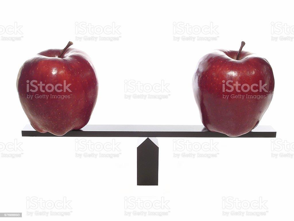 Metaphor compairing Apples balanced on beam. stock photo