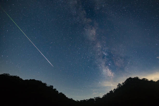 a meteor shoots across the night sky sky leaving a trail of light across the milky way - shooting stars stock photos and pictures