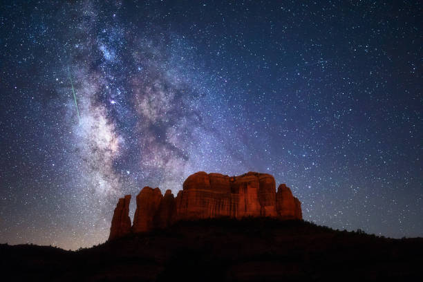 Meteor streaks through the Milky Way above Cathedral Rock in Sedona, Arizona. stock photo