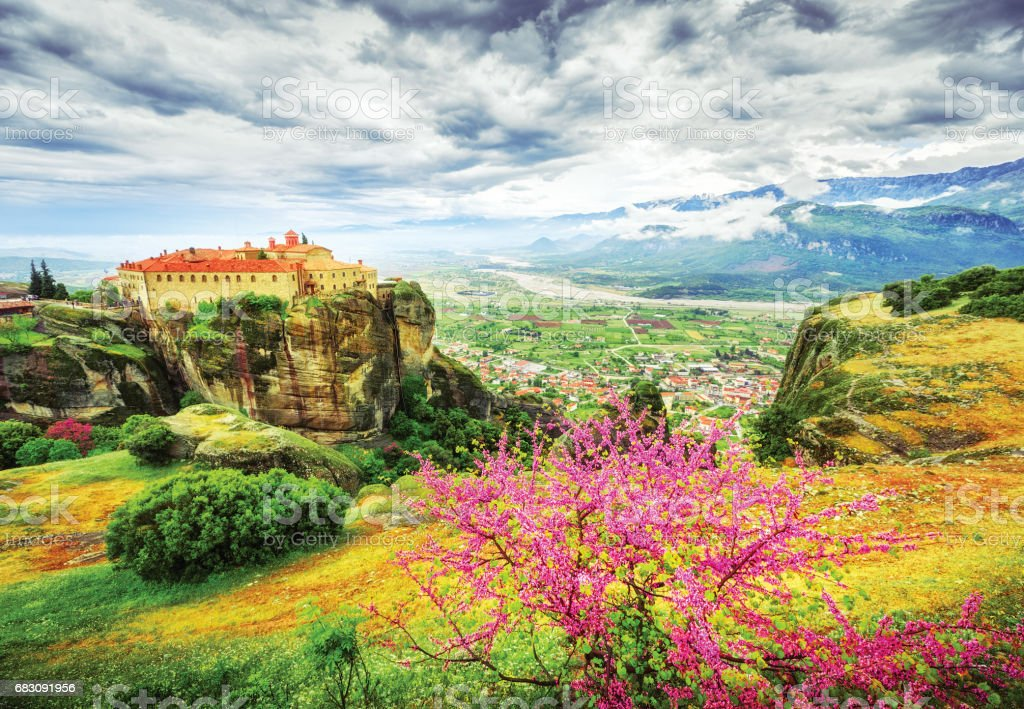 Meteora monasteries in Greece, spring scenery with red blooming tree in foreground, fantastic epic sky in background. stock photo