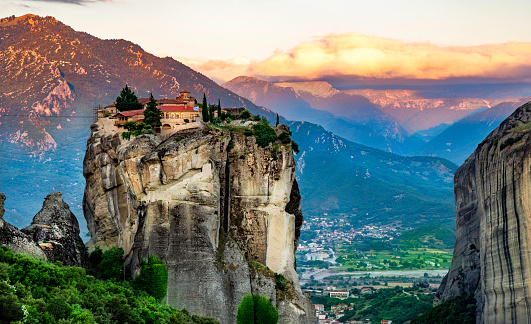 Panoramic view of Meteora mountain and religios monastery of Greece illuminated in sunset light