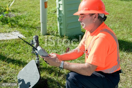 Water utility worker is checking the water meter with a handheld device to make sure everything is working.