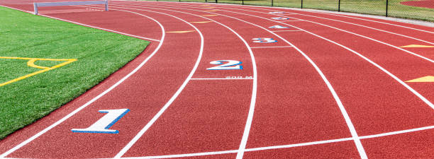 200 meter start line on a red track Landscape view of a red track with white numbers that have blue trim at the two hundred meter start. high school sports stock pictures, royalty-free photos & images