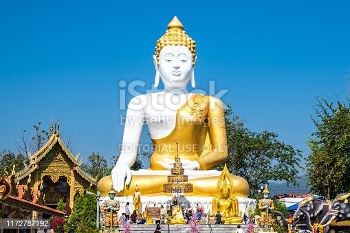 Chiangmai, Thailand - February 24, 2019: View of Thai pilgrimage traveler with 17 Meters tall sitting Buddha at Wat Phra That Doi Kham temple in Chiangmai, Thailand.