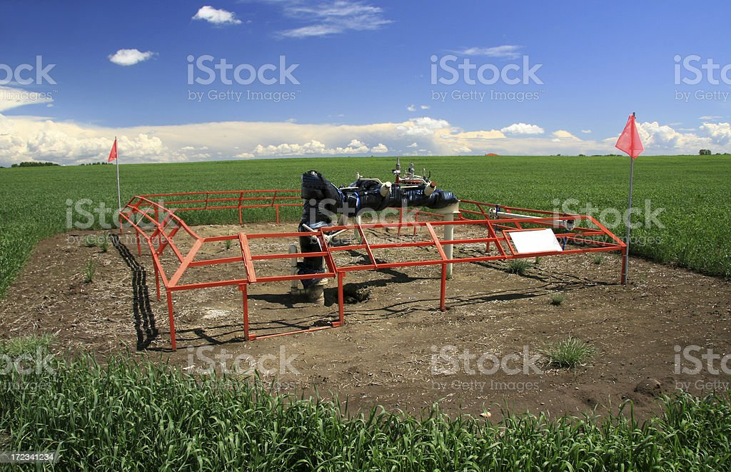 A methane gas well surrounded by red fence and a huge field royalty-free stock photo