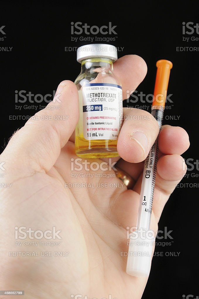 Methotrexate in hand with syringe stock photo