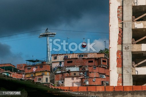 photography of a cable car inside a neighborhood in the city of Caracas, which shows many houses of low socioeconomic status. In the middle of the image is the support post for the aerial cable system and other buildings in the middle of an architectural anarchy