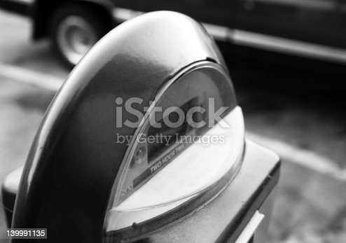 This is a parking meter in a busy cityscape enviornment. It's in a black and white format.