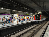 Barcelona, Spain - 10/07/2017: The picture shows a subway station in Barcelona with the metro coming and a crowd waiting.