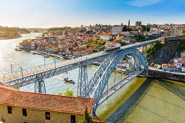 metro travelling accross the dom luis i bridge in porto - portugal stock photos and pictures