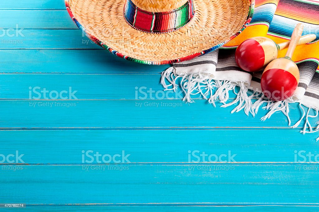 Mexican sombrero and maracas with traditional serape blanket laid on...