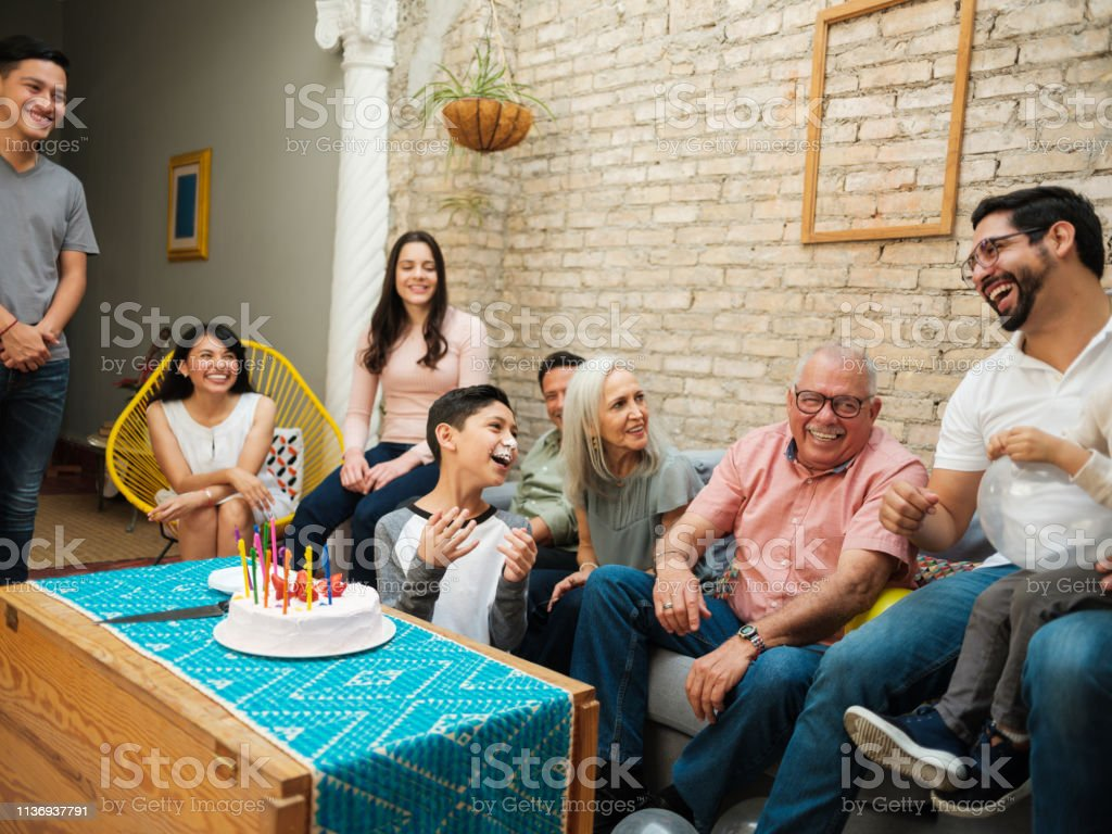 Mexican boy with cake on face A mexican boy sitting with his family, having cake on his face and laughing. Adolescence Stock Photo