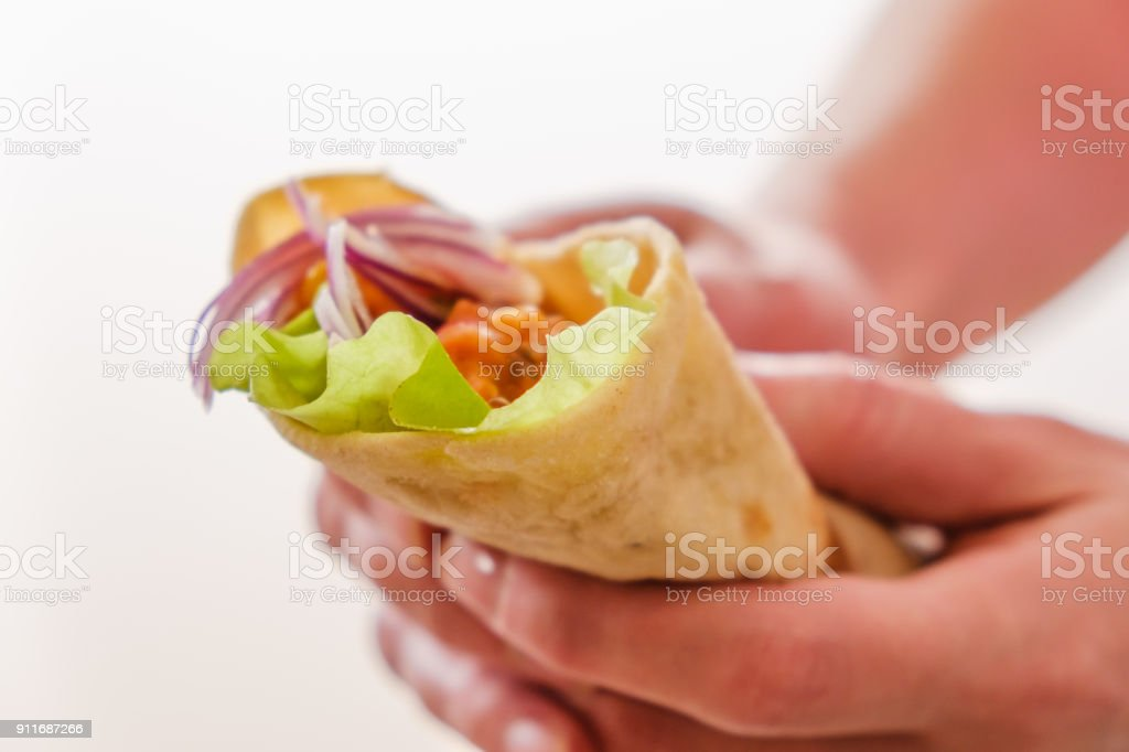 Mexican burrito in hand with chicken, pepper and beans stock photo