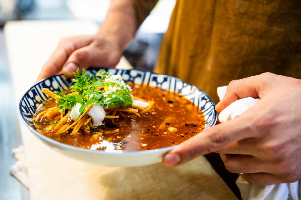 Mexican chef serving Aztec soup in an authentic Mexican restaurant stock photo