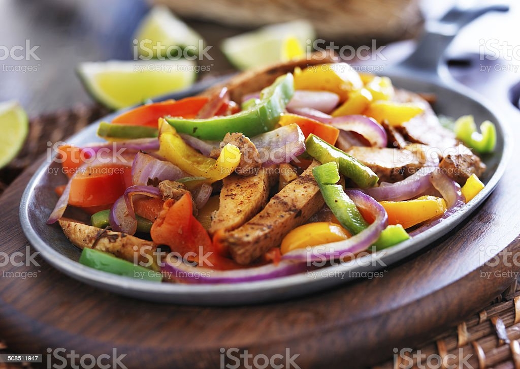 mexican chicken fajitas in iron skillet with peppers stock photo