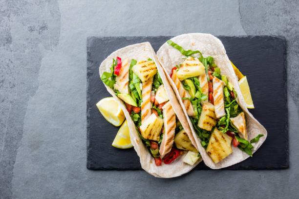 mexikanisches huhn tacos mit gegrillter ananas und gemüse auf schiefer grau hinterlegt - ananas huhn salate stock-fotos und bilder