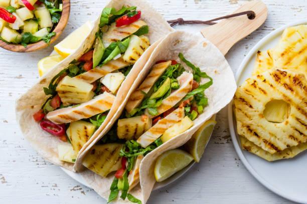 mexikanisches huhn tacos mit gegrillter ananas und gemüse auf weißem hintergrund - ananas huhn salate stock-fotos und bilder