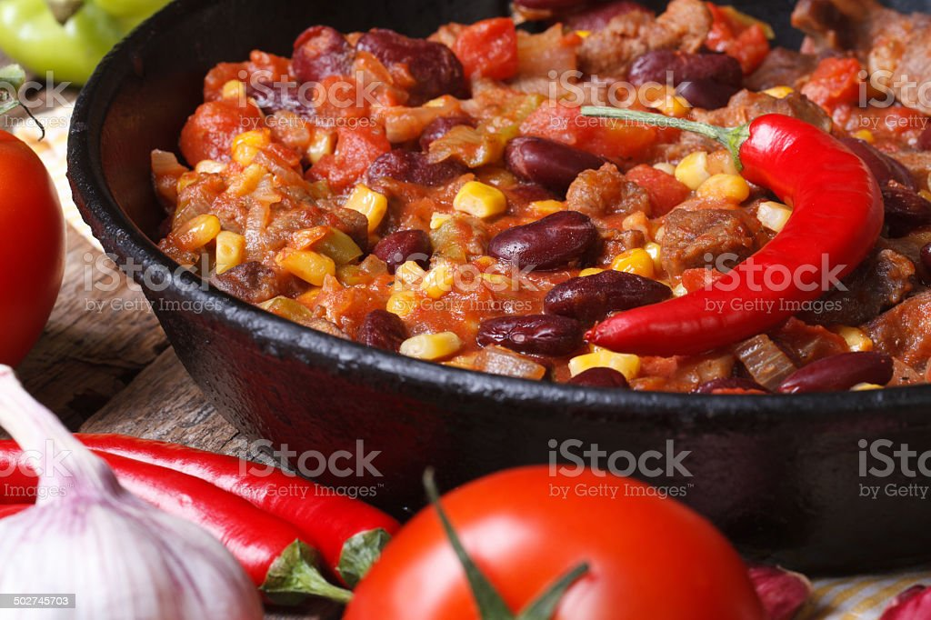 Mexican chili con carne in a pan on a wooden stock photo