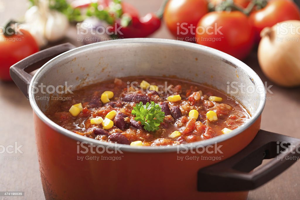 mexican chili con carne in red rustic pot with ingredients stock photo