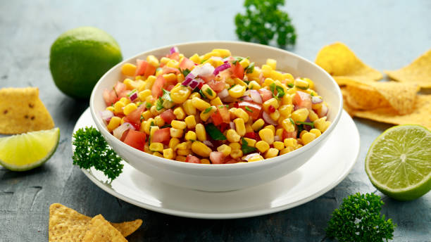 Mexican Corn Salsa in white bowl with lime and tortilla chips. Healthy food stock photo