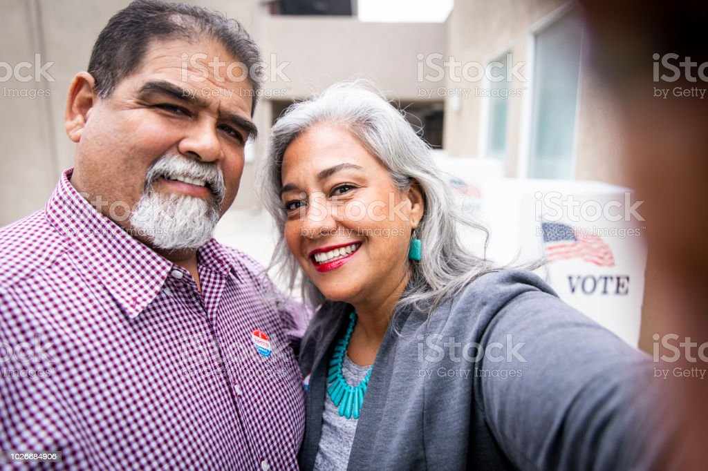 Mexican Couple Taking a Selfie at Voting Booth stock photo