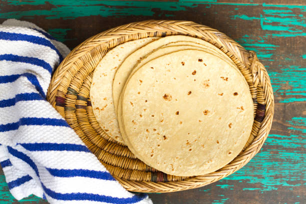 mexican cuisine: corn tortillas in basket; distressed table - tortilla stock photos and pictures