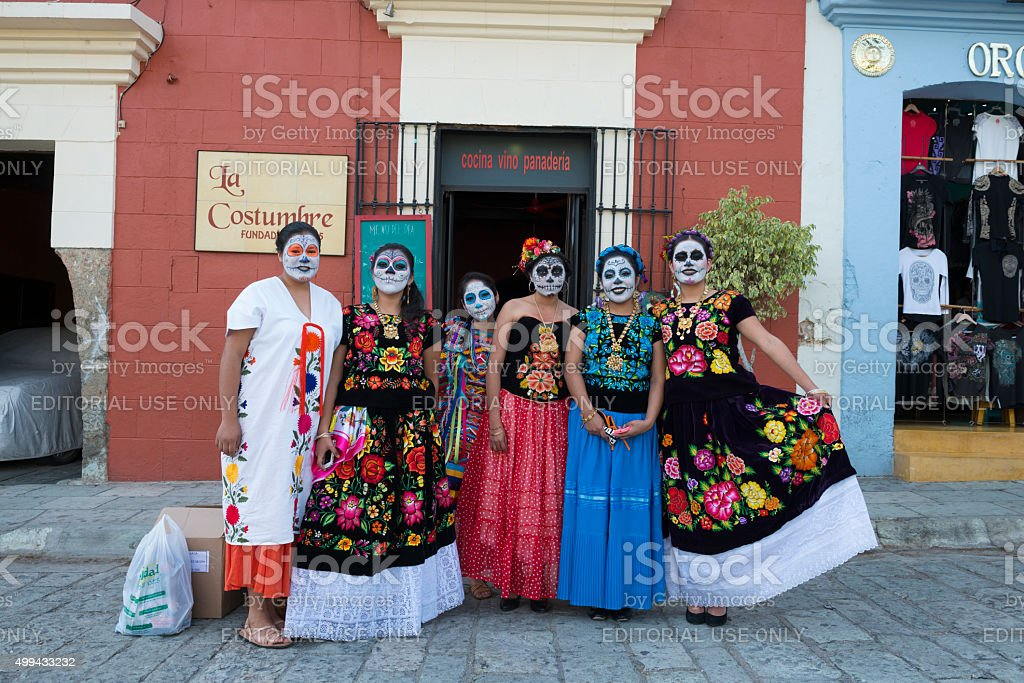 A group of Mexican women stand together on the street in Oaxaca,...