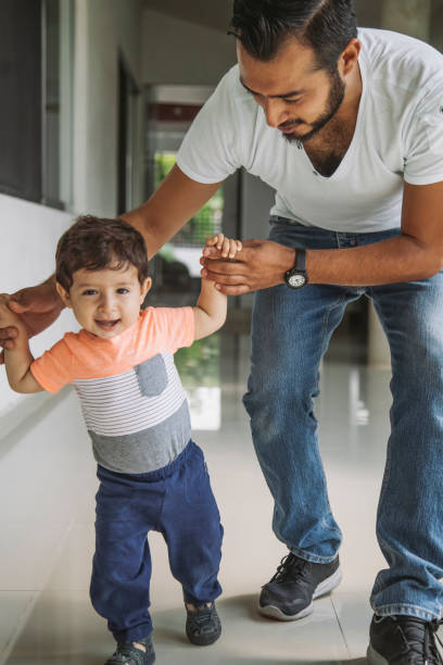 Mexican dad helping his baby boy take his first steps, learning to walk stock photo