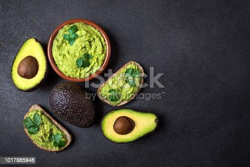 istock Mexican Dip Sauce Guacamole with avocado  in a clay bowl  on black background. Avocado spread. Top view. Copyspace